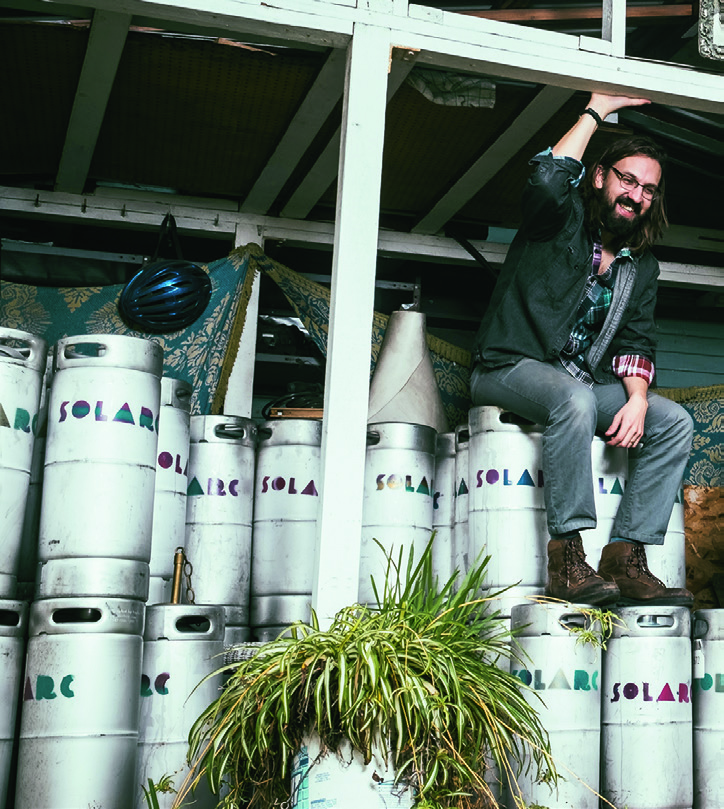 Archie Carey Sitting on a Pile of Barrels at the Brewery