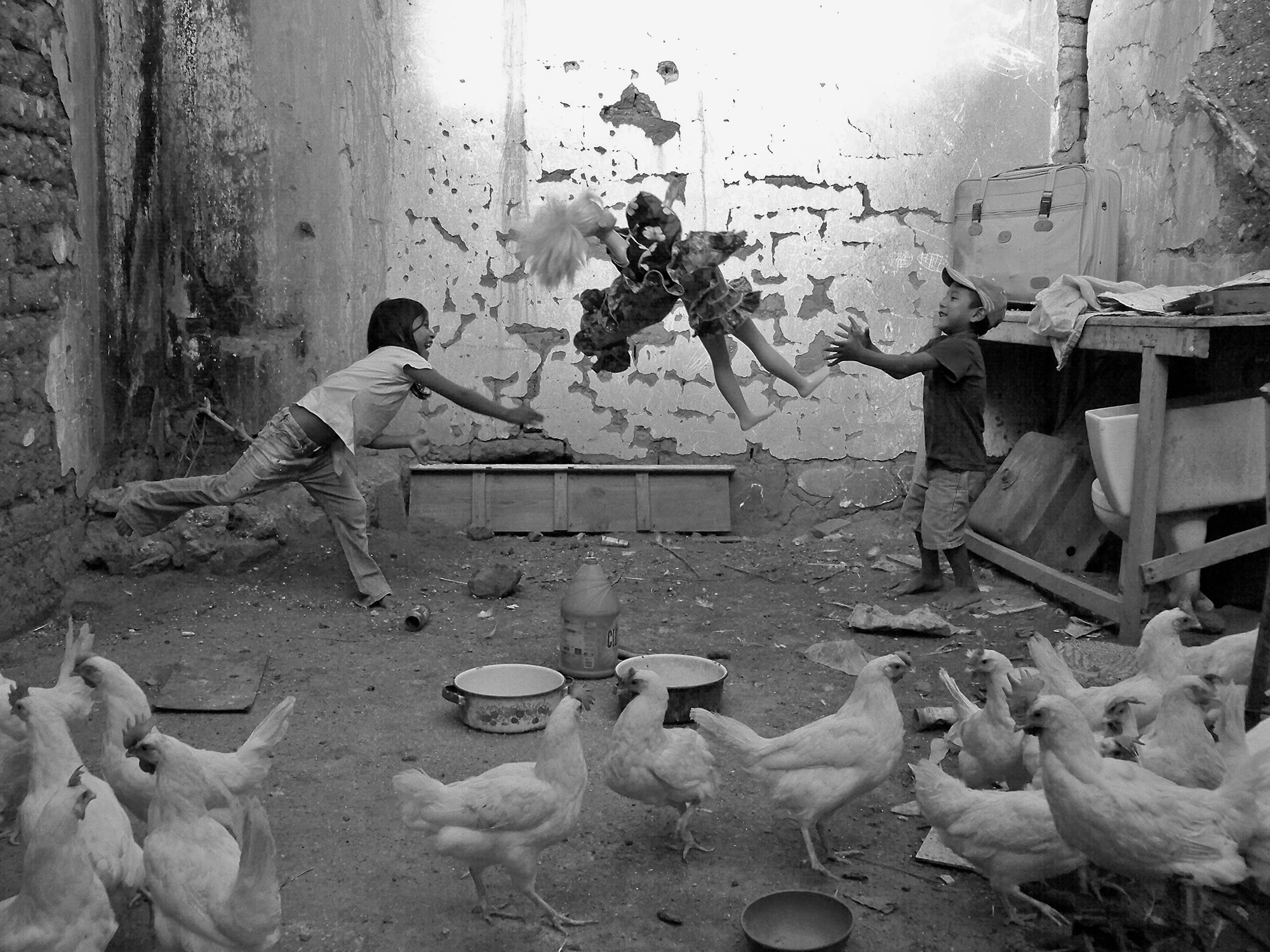 Joel Orozco, Beyond the Mask: Children inside a chicken coop, throwing doll in the air