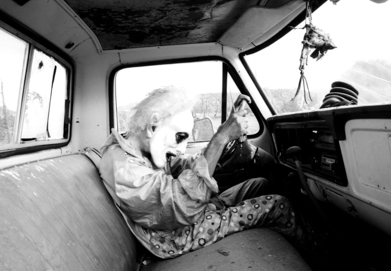 Joel Orozco, Beyond the Mask: Man wearing a mask inside a car holding the stirring wheel with sharp object