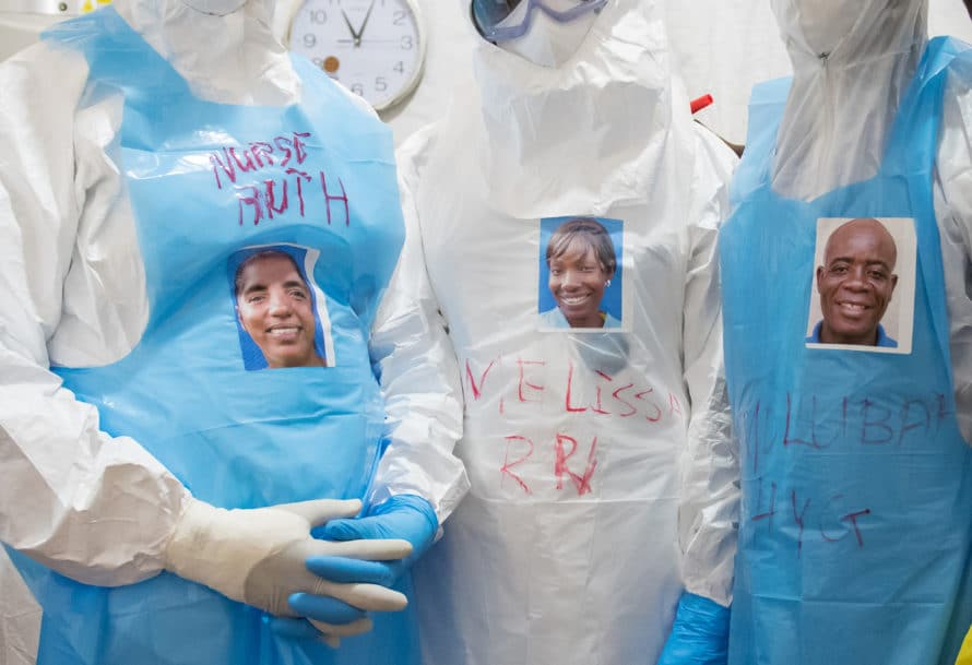 "Wearing stickers with their faces on them, health care workers prepare to enter the ""red zone"" to care for unconfirmed Ebola patients in the ELWA II ETU (Ebola treatment unit), Monrovia, Liberia on Friday, March 6, 2015. Occidental College professor Mary Beth Heffernan's PPE Portrait Project involves creating wearable portraits of the health care workers who must wear PPE (personal protective equipment) when working with patients. Photo by Marc Campos, Occidental College Photographer"